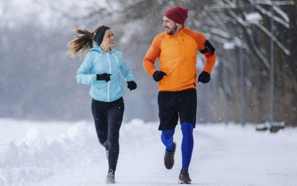 Man wearing orange sweater and running in winter with woman wearing blue sweater