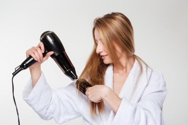 blonde woman blow drying her hair