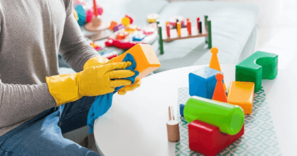 wearing yellow rubber gloves and sanitizing kids toys