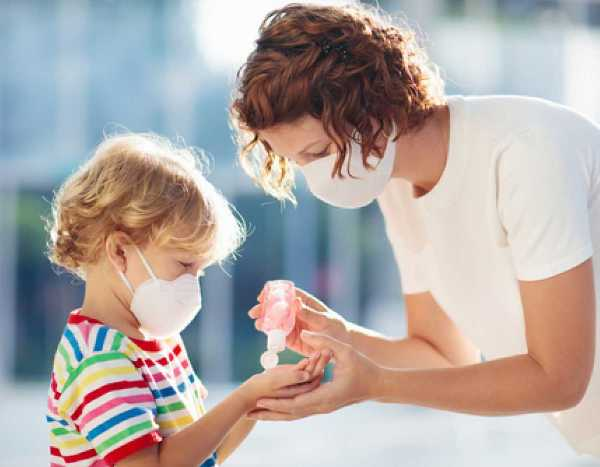 woman and child wearing masks and sanitizing hands for coronavirus