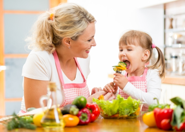 mother feeding her daughter salad